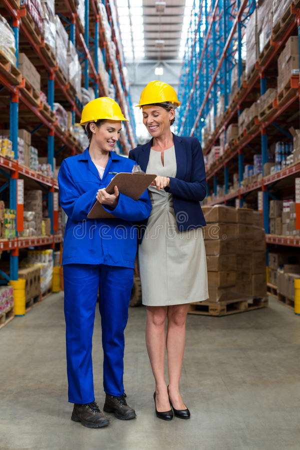 Warehouse manager and worker discussing with clipboard royalty free stock photo