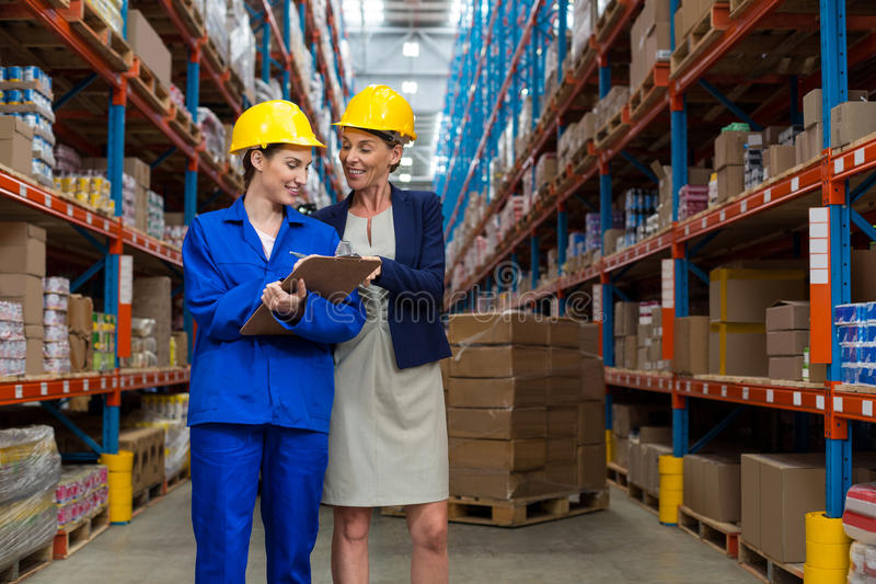 Warehouse manager and worker discussing with clipboard. In warehouse stock images