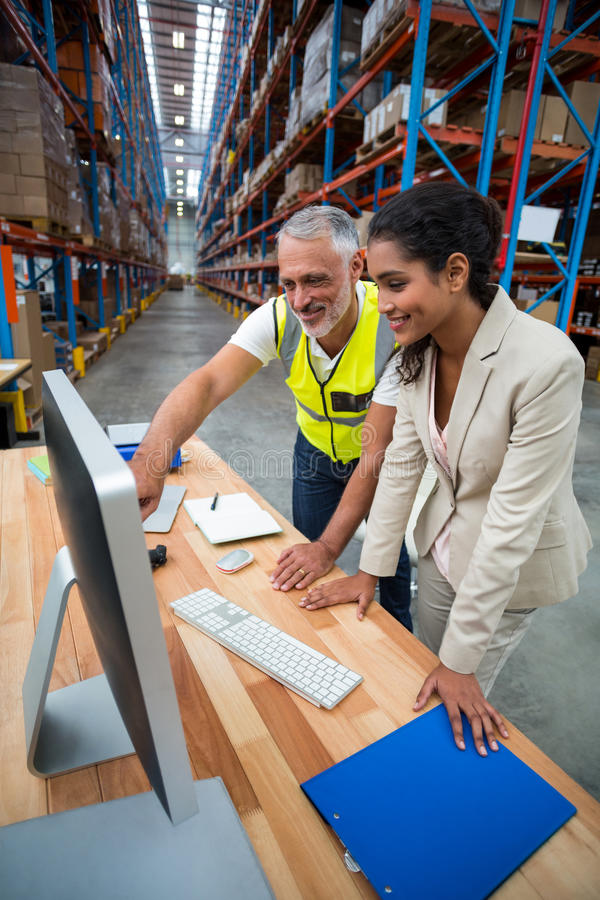 Warehouse manager and worker discussing with computer. In warehouse office royalty free stock images