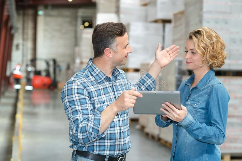 Warehouse manager and worker looking at tablet in warehouse stock photography