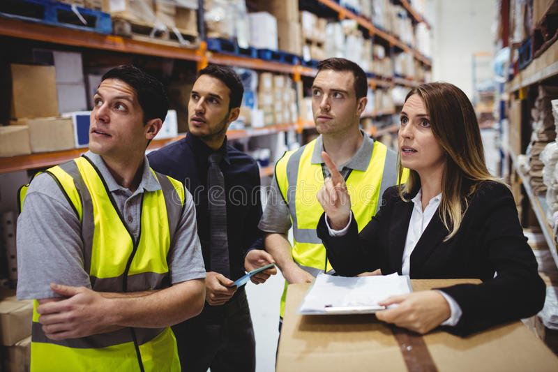 Warehouse manager and workers talking. In the warehouse stock photos