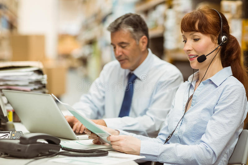 Warehouse manager working at her desk wearing headset. In a large warehouse royalty free stock images