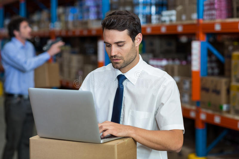 Warehouse manager working on laptop royalty free stock photo