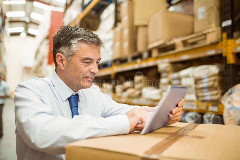 Warehouse manager working on tablet pc. In a large warehouse stock photos