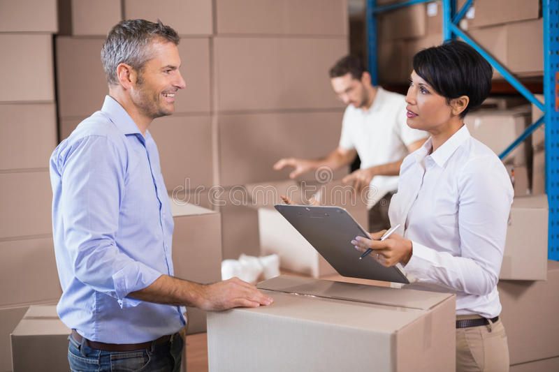 Warehouse manager writing on clipboard talking to colleague. In a large warehouse royalty free stock photography