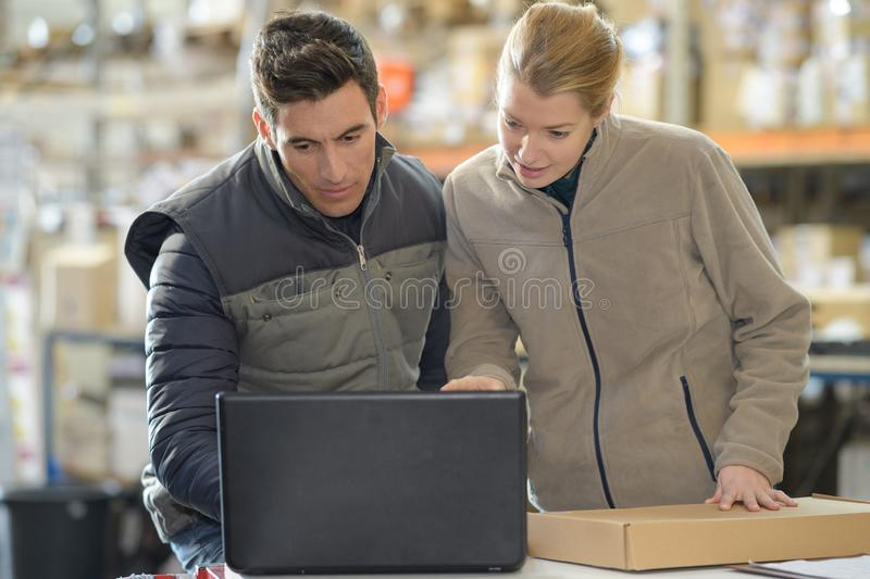 Warehouse managers using laptop in warehouse royalty free stock images