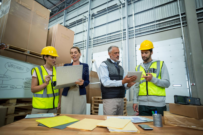 Warehouse managers and workers discussing with laptop and digital tablet stock photos