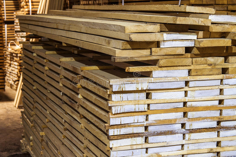 Warehouse packed with variety of timber for construction and rep. Air. Wood timber construction material royalty free stock photos
