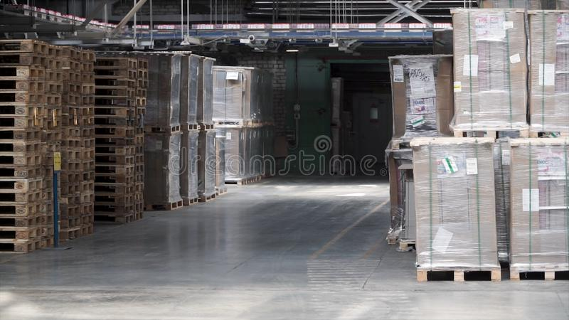 Warehouse with racks and shelves, filled with cardboard boxes, wrapped in foil on wooden pallets. Clip. Large and light stock images