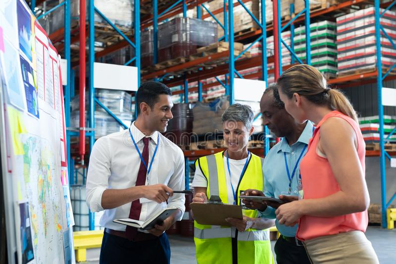 Warehouse staffs discussing over clipboard in warehouse. Front view of diverse warehouse staffs discussing over clipboard in warehouse. This is a freight royalty free stock photo