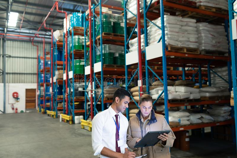 Warehouse staffs discussing over digital tablet in warehouse. Front view of Caucasian warehouse staffs discussing over digital tablet in warehouse. This is a royalty free stock photos