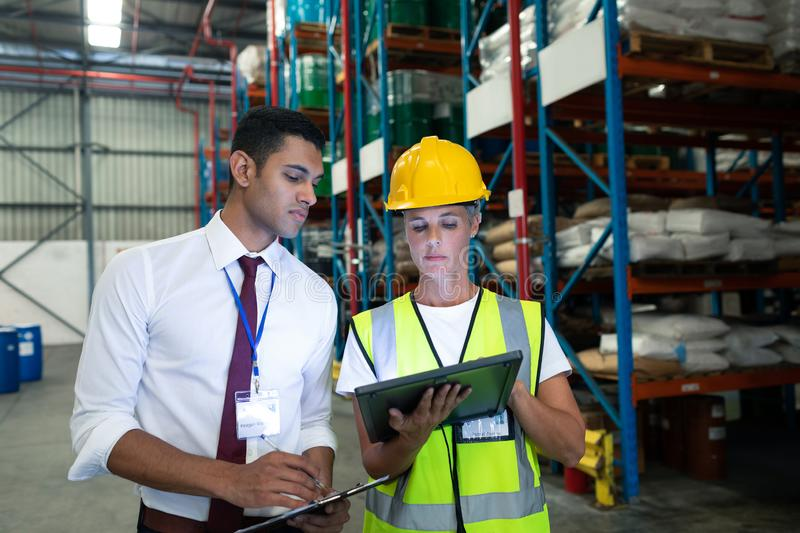 Warehouse staffs discussing over digital tablet in warehouse. Front view of diverse Attentive warehouse staffs discussing over digital tablet in warehouse. This stock photography