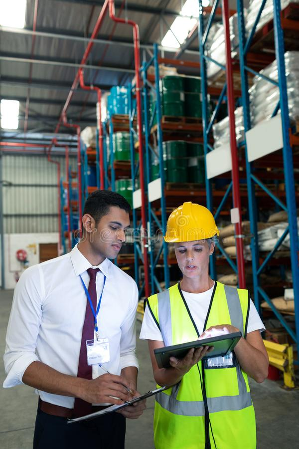 Warehouse staffs discussing over digital tablet in warehouse. Front view of diverse Attentive warehouse staffs discussing over digital tablet in warehouse. This royalty free stock photo