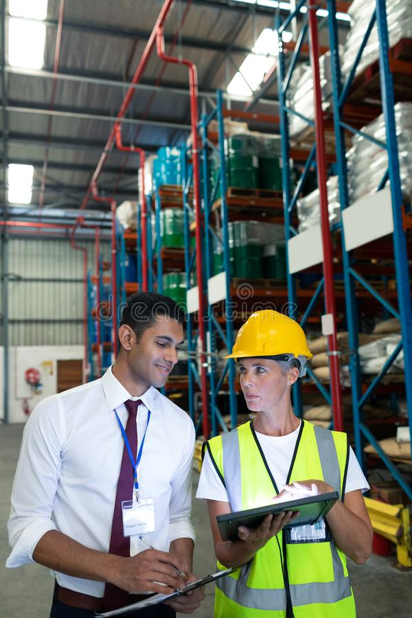 Warehouse staffs discussing over digital tablet in warehouse. Front view of diverse Attentive warehouse staffs discussing over digital tablet in warehouse. This stock image