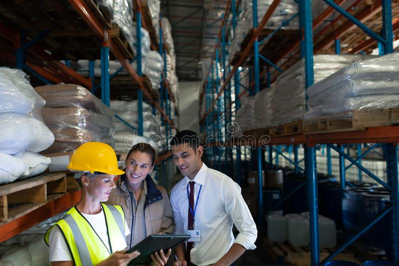 Warehouse staffs discussing over digital tablet in warehouse. Front view of diverse staffs discussing over digital tablet in warehouse. This is a freight stock images