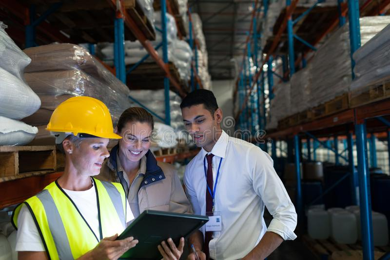 Warehouse staffs discussing over digital tablet in warehouse. Front view of diverse staffs discussing over digital tablet in warehouse. This is a freight royalty free stock photos