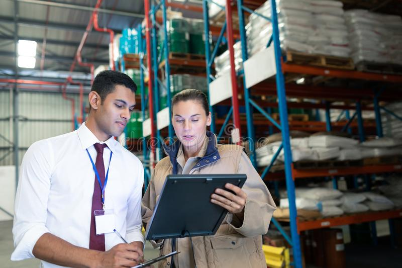 Warehouse staffs discussing over digital tablet in warehouse. Front view of diverse staffs discussing over digital tablet in warehouse. This is a freight royalty free stock images