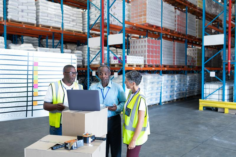 Warehouse staffs discussing over laptop in warehouse. Front view of mature diverse warehouse staffs discussing over laptop in warehouse. This is a freight royalty free stock photography