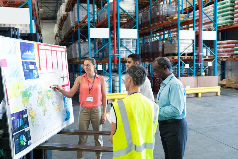 Warehouse staffs discussing over whiteboard in warehouse. Front view of diverse warehouse staffs discussing over whiteboard in warehouse. This is a freight stock photos