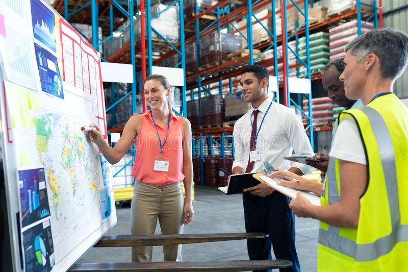 Warehouse staffs discussing over whiteboard in warehouse. Front view of diverse warehouse staffs discussing over whiteboard in warehouse. This is a freight stock image