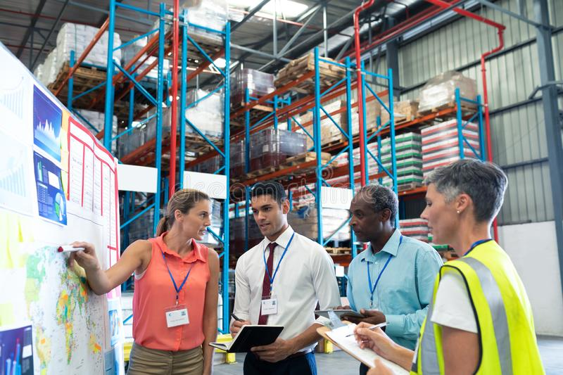 Warehouse staffs discussing over whiteboard in warehouse. Front view of diverse warehouse staffs discussing over whiteboard in warehouse. This is a freight stock photo