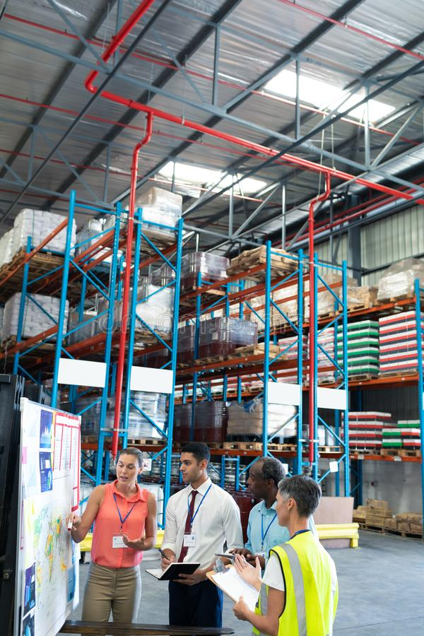 Warehouse staffs discussing over whiteboard in warehouse. Front view of diverse warehouse staffs discussing over whiteboard in warehouse. This is a freight royalty free stock photos