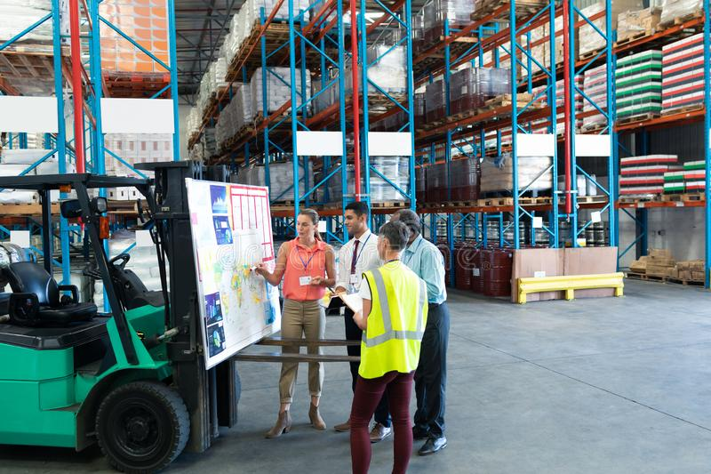 Warehouse staffs discussing over whiteboard in warehouse. Front view of diverse warehouse staffs discussing over whiteboard in warehouse. This is a freight stock photography