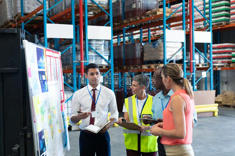 Warehouse staffs discussing over whiteboard in warehouse. Front view of diverse warehouse staffs discussing over whiteboard in warehouse. This is a freight royalty free stock images