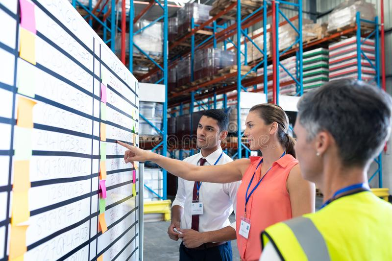 Warehouse staffs discussing over whiteboard in warehouse. Side view of diverse warehouse staffs looking at whiteboard in warehouse. This is a freight stock images