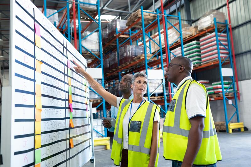 Warehouse staffs discussing over whiteboard in warehouse. Side view of mature diverse warehouse staffs discussing over whiteboard in warehouse. This is a freight royalty free stock image