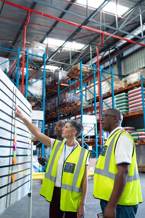 Warehouse staffs discussing over whiteboard in warehouse. Side view of mature diverse warehouse staffs discussing over whiteboard in warehouse. This is a freight stock photos
