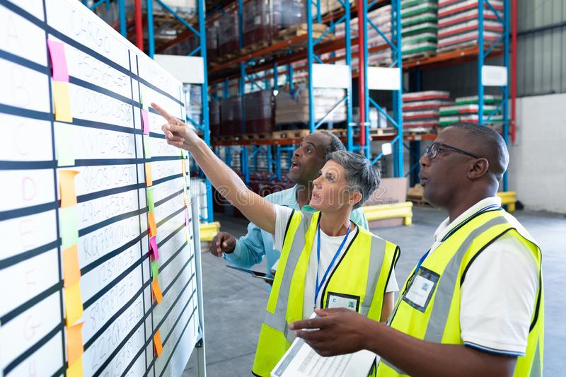 Warehouse staffs discussing over whiteboard in warehouse. Side view of mature diverse warehouse staffs discussing over whiteboard in warehouse. This is a freight stock images
