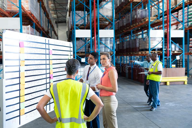 Warehouse staffs interacting with each other in warehouse. Front view of diverse warehouse staffs interacting with each other in warehouse. This is a freight stock photo