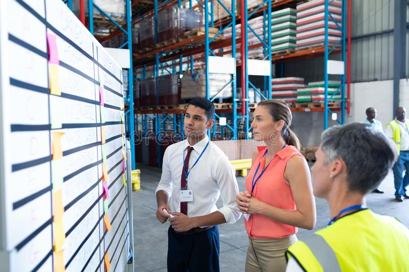 Warehouse staffs looking at whiteboard in warehouse. Front view of diverse warehouse staffs looking at whiteboard in warehouse. This is a freight transportation stock photography