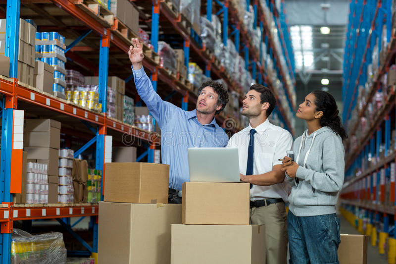 Warehouse, storehouse, storage, goods, stock, worker, manager, staff, colleagues, team, well dressed. Warehouse manager and worker discussing with laptop in stock photography