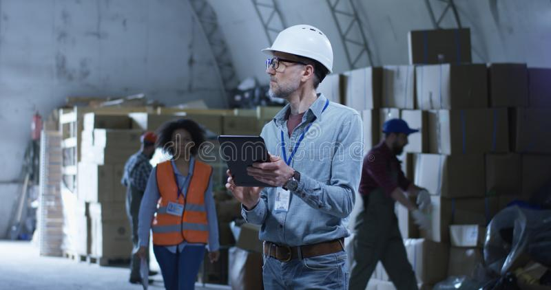 Warehouse supervisor overseeing staff. Medium long shot of warehouse supervisor overseeing staff stock photography
