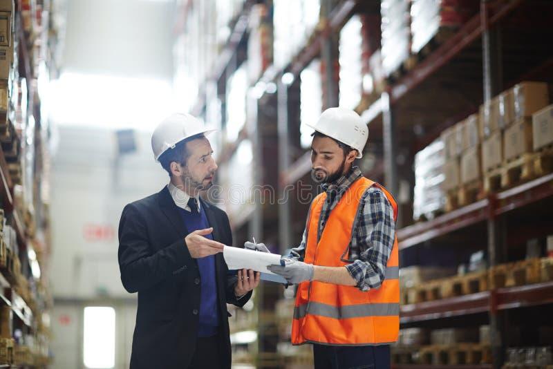 Warehouse Supervisor Talking with Order Builder stock image