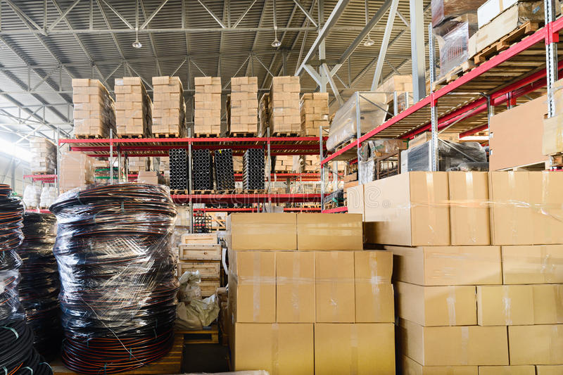 Warehouse transport and freight company. In the foreground a pile of cardboard boxes and a coil of plastic tubing stock photography