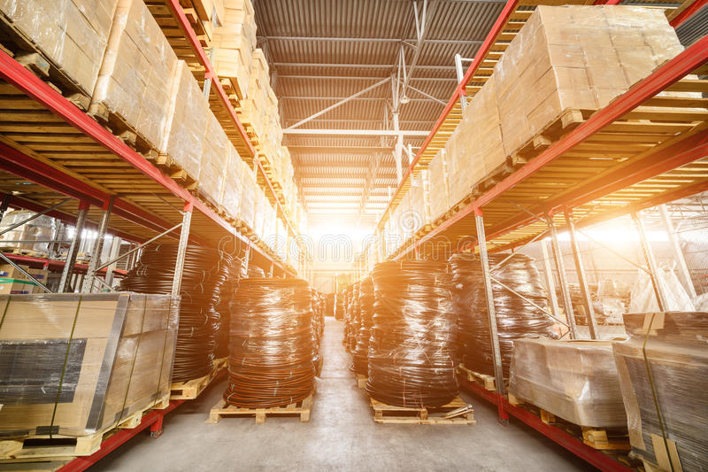 Warehouse transport and freight company. In the foreground a pile of cardboard boxes and a coil of plastic tubing. Bright sunlight stock photos