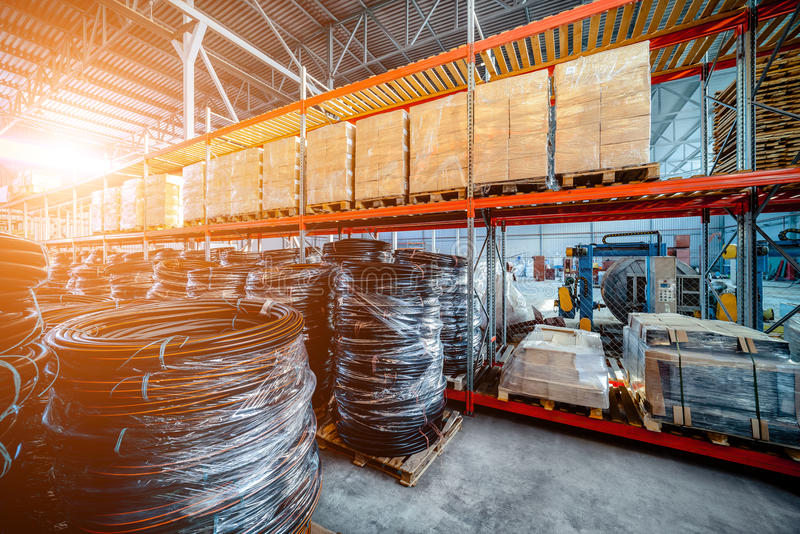 Warehouse transport and freight company. In the foreground a pile of cardboard boxes and a coil of plastic tubing. Toning the image. Bright sunlight stock photography