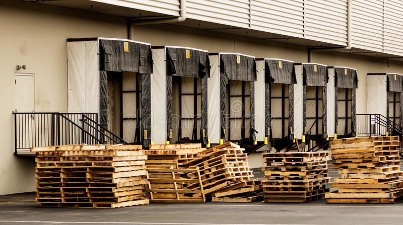 Warehouse truck bays with stacked wooden pallets stock images