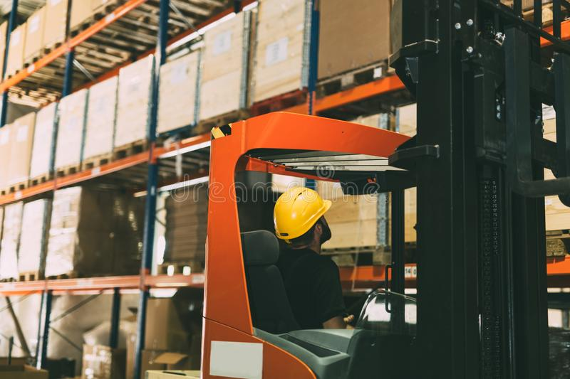 Warehouse worker doing logistics work with forklift loader stock photography