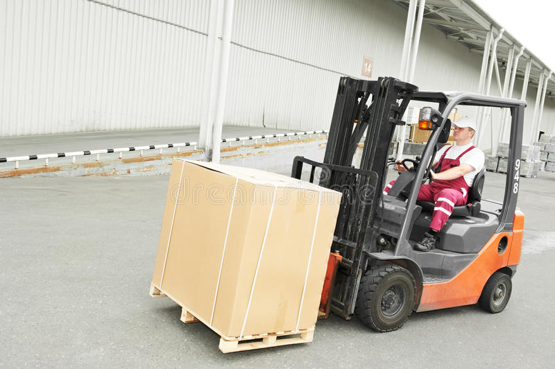Warehouse worker driver in forklift. Young cheerful warehouse worker driver in uniform driving forklift stacker loader royalty free stock images