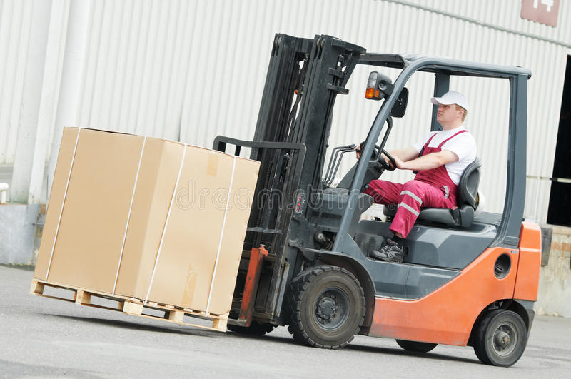 Warehouse worker driver in forklift. Young cheerful warehouse worker driver in uniform driving forklift stacker loader royalty free stock photo