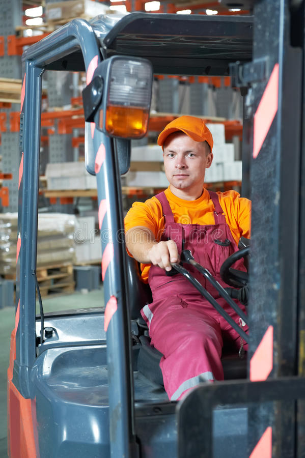 Warehouse worker driver in forklift. Young cheerful warehouse worker driver in uniform driving forklift stacker loader stock photo