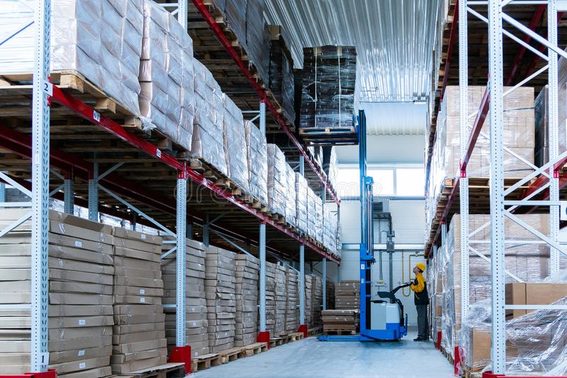 Warehouse worker driver in uniform delivery and loading cardboxes by forklift stacker loader royalty free stock photography