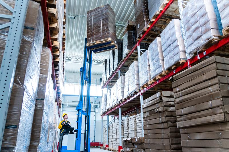 Warehouse worker driver in uniform delivery and loading cardboxes by forklift stacker loader stock images