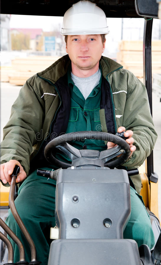 Warehouse worker in forklift. Wearing a white helmet stock image