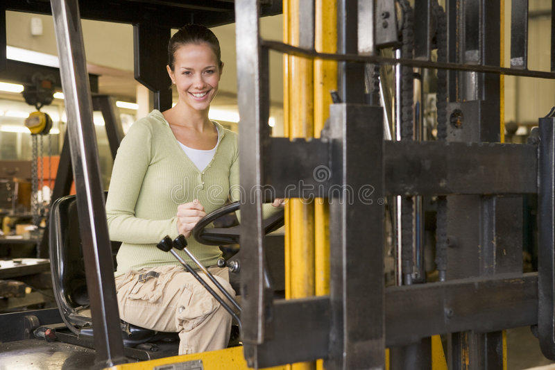 Warehouse worker in forklift. Warehouse worker driving a yellow forklift stock photo