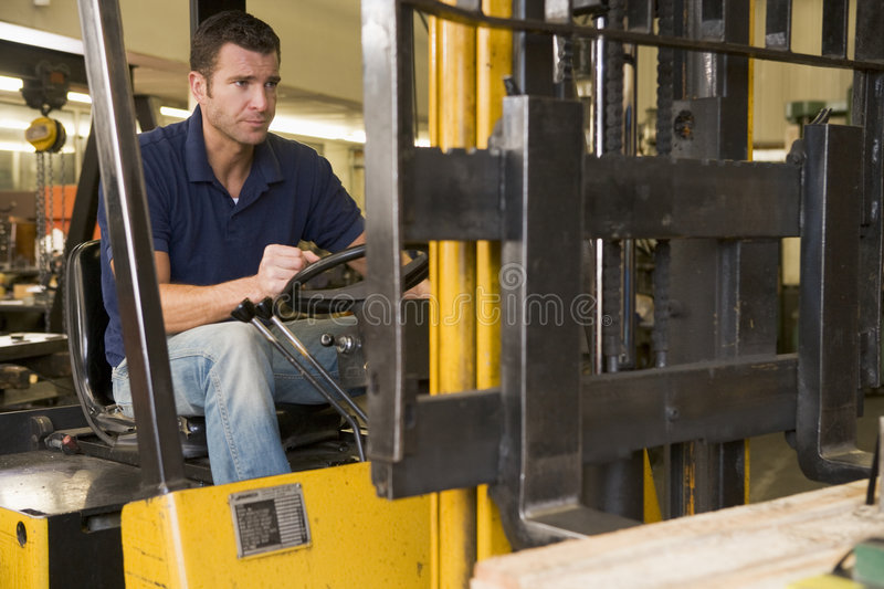 Warehouse worker in forklift stock photography